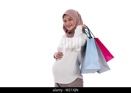 woman pregnant show lots of shopping bags after buying in an isolated background - Stock Image