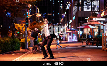 smiling businessman dancing on street in city at night - Stock Image