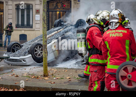 Paris, France. 1st December, 2018.  Firefighters extenguishing a car on fire during the Yellow Vests protest against Macron politic. Credit: Guillaume Louyot/Alamy Live News - Stock Image