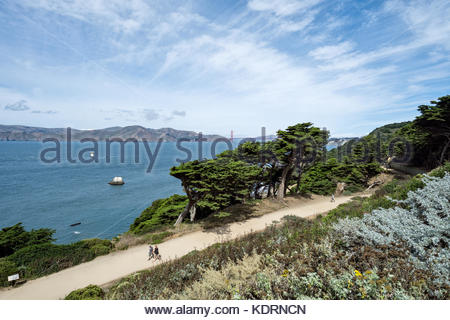 Hikers on the Coastal Trail at Land's End in San Francisco, California, enjoy sweeping views of the Golden Gate. - Stock Image