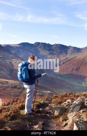 Female hill walker map reading on Side Pike with Oxendale and Crinkle Crags in the distance, Langdale,Lake District, England, UK - Stock Image