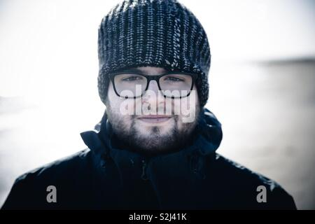 A young man with beard and glasses wearing a warm woolly hat and warm coat looking directly into the camera like an explorer or outdoor adventurer - Stock Image