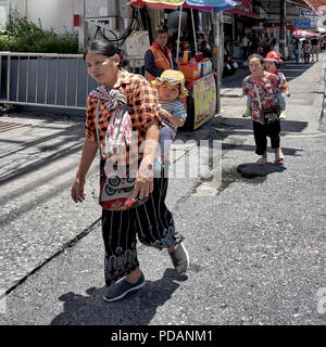 Thai women carrying their children in a back sling. Thailand street scene, Southeast Asia - Stock Image