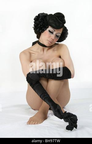 Portrait of a Burlesque Performer Sitting Cross Legged on the Floor - Stock Image