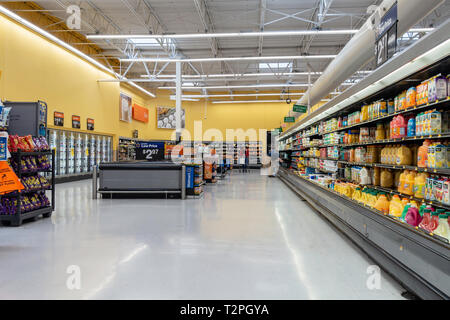 Interior of Walmart store with a woman shopper and a male employee stocking shelves. USA - Stock Image
