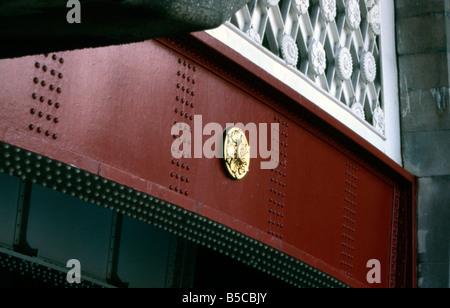Bridge England gold London medallion metal ornate railing red rivets steel structural white - Stock Image