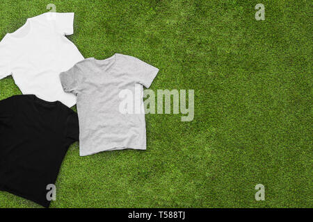 Randomly scattered mens different coloured T-shirts on grass background. Horizontal view. - Stock Image