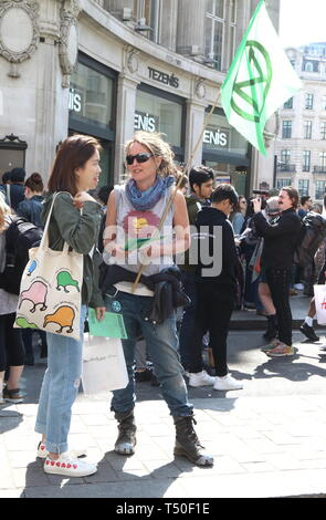 London, UK. 19th Apr, 2019. Activist seen with leaflets during the demonstration.Environmental activists from Extinction Rebellion movement occupy London's Oxford Circus for a 5th day. Activists parked a pink boat in the middle of the busy Oxford Circus road junction blocking the streets and causing traffic chaos. Credit: Keith Mayhew/SOPA Images/ZUMA Wire/Alamy Live News - Stock Image