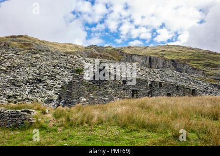 Ruined industrial building below slag heap in Gorseddau slate quarry in Cwmystradllyn in Snowdonia National Park. Porthmadog, Gwynedd, Wales, UK - Stock Image