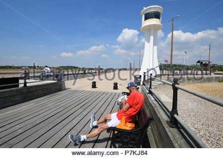 Littlehampton, UK. Saturday 7th July 2018. A man reads the Daily Mirror newspaper by the lighthouse on a very warm afternoon in Littlehampton, on the South Coast. Credit: Geoff Smith / Alamy Live News. - Stock Image