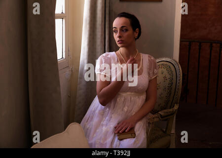 Young woman in authentic regency dress near a window of a classical interior - Stock Image