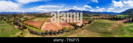 New England highway through green valley of upper Hunter Valley and horse farms between distant hill ranges - wide aerial panorama. - Stock Image