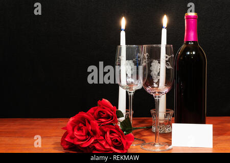 Beautiful etched wine glasses and bottle of red wine, white candles and red roses on wooden table with name tag on dark background. Valentines, Mother - Stock Image