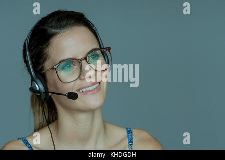 Young woman wearing headset, smiling cheerfully - Stock Image