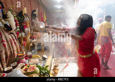 A devout Hindu worshipper performs the ritual of AARTI, passing flames in front of statues of deities. In  Queens, New York City. - Stock Image