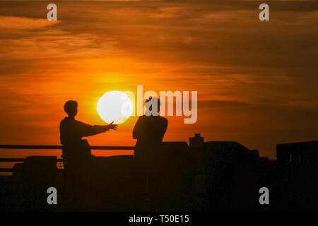 London. 19th Apr 2019. UK Weather: London, UK, 19th April 2019. Two people are silhouetted against a beautiful sunset by the River Thames at London's South Bank. Following a day of blue skies and unusually warm temperatures, the rest of the Easter weekend is forecast to see similarly pleasant weather. Credit: Imageplotter/Alamy Live News - Stock Image