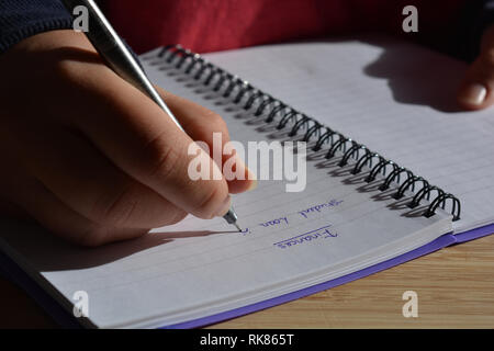 Millennial woman writing in a spiral bound notebook, pen in hand.  A List headed with the word Finances, and beneath that is written Student Loan - Stock Image