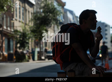 Tourist eating ice cream on a hot summer day outside of the Chocolate Shop and Museum on Rue Saint-Jean in old Québec City, Canada - Stock Image