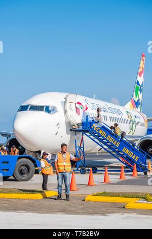 Passengers board Cayman Airways flight from Juan Manuel Galvez Airport Roatan Honduras. - Stock Image