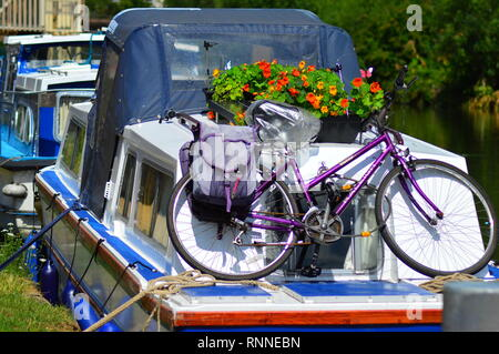 Purple bicycle on board a canal boat - Stock Image