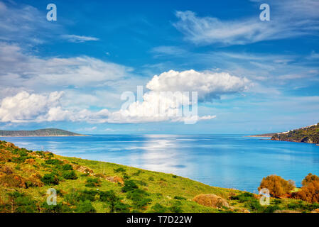 Beautiful calm sea, meadow field, clouds, sky and island landscape of a holiday place in Cukurbuk bay, Bodrum, Mugla, Turkey - Stock Image