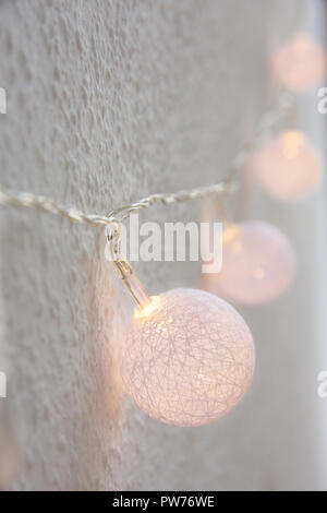 Christmas New Year Background. Hanging Pastel Golden Cotton Balls Garland White Wall Background. Scandinavian Style. Glittering Lights. Cozy Festive A - Stock Image