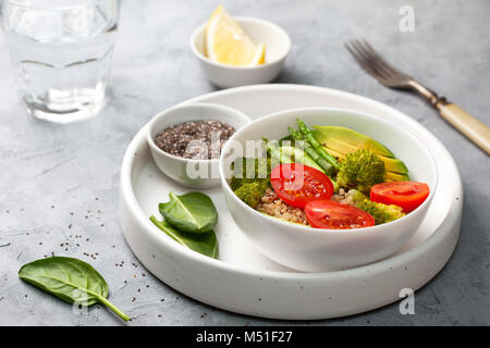 diet healthy breakfast. quinoa and vegetables: tomatoes, asparagus, broccoli, avocado and spinach, chia seeds in - Stock Image