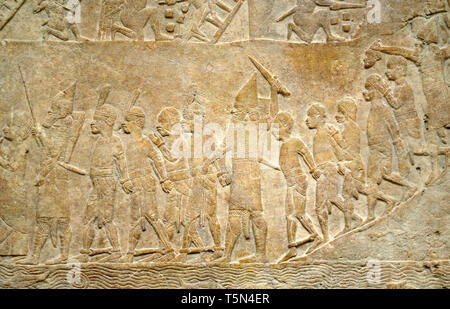 British Museum, Bloomsbury, London, England, UK. Gypsum panel showing the Assyrian army attacking the Egyptian city of Memphis, the final victory of K - Stock Image