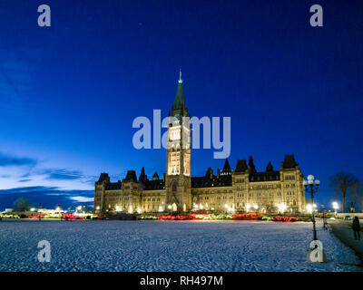 Canada's Parliament Buildings at night: A floodlit view of the centre block on a cold winter night. There's snow on the hill and the building is floodlit against a deep blue sky. - Stock Image