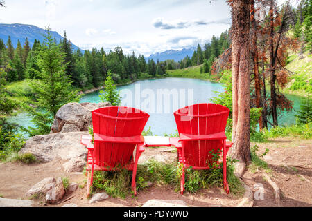 Two red adirondack chairs overlooking the Valley of the Five Lakes on the Icefields Parkway in the Canadian Rockies. They were placed by Parks Canada  - Stock Image
