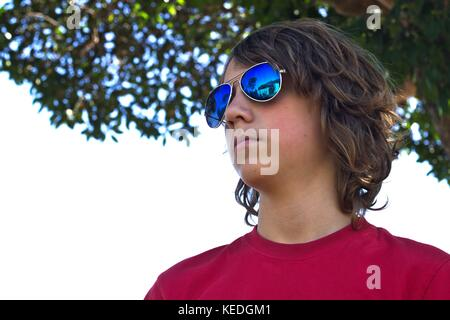 Young teenage male wearing blue sunglasses head shot against suburban background. - Stock Image