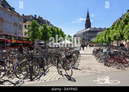 Typical scene with lots of bicycles parked by cycle lane sign in Hojbro Plads, Copenhagen, Zealand, Denmark - Stock Image