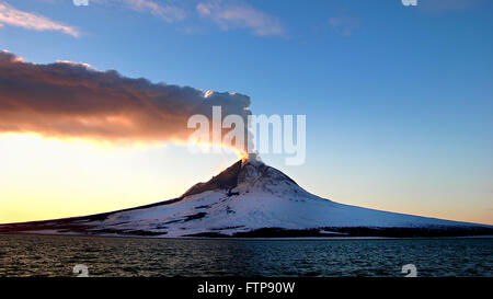 A steam plume rises into the sky from the lava dome at the summit of Augustine Volcano at sunrise on Augustine Island - Stock Image