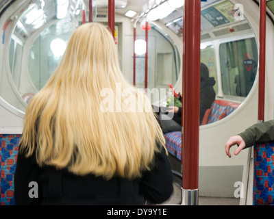A blond woman on a tube train in London UK - Stock Image