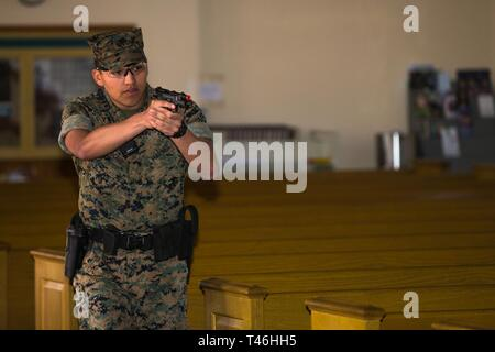 U.S. Marine Corps Lance Cpl. Angel Trejocruz, military police officer with the Provost Marshal's Office, Security and Emergency Services Battalion, Marine Corps Base (MCB) Camp Pendleton, searches the Marine Memorial Chapel during an active-shooter drill at MCB Camp Pendleton, California, March 12, 2019. The purpose of the drill was to ensure readiness in the event of an active shooter on the installation. - Stock Image