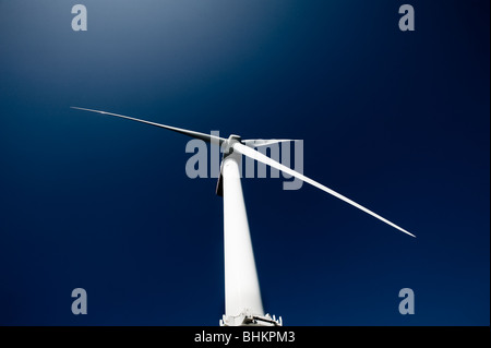 image of offshore wind turbine against blue sky - Stock Image