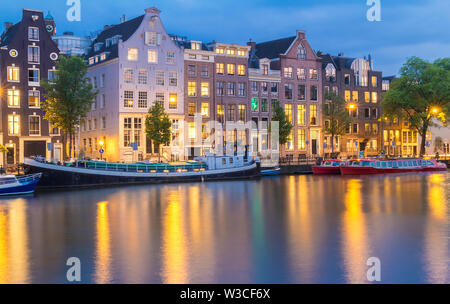 Night city view of Amsterdam canal, typical dutch houses and boats, Holland, Netherlands. - Stock Image