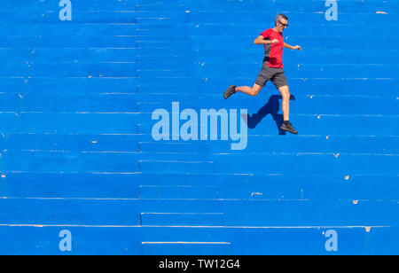 Fit 62 year old man running down blue steps in public park. - Stock Image