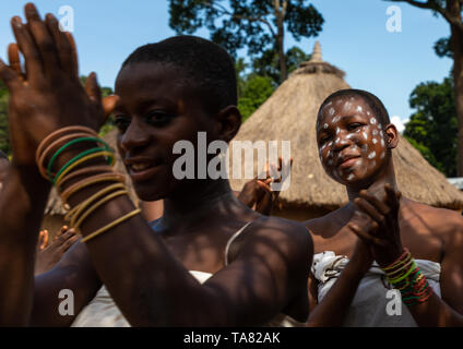 Dan tribe young women clapping hands and dancing during a ceremony, Bafing, Gboni, Ivory Coast - Stock Image