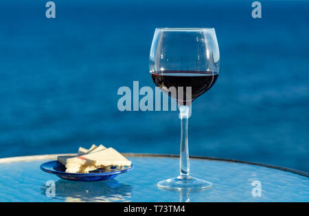 Aperitif, red wine in glasses served with cheese on outdoor tessace witn sea view close up - Stock Image