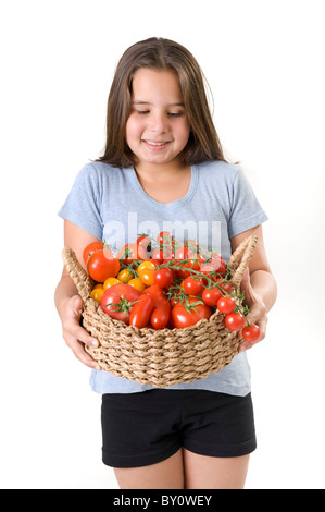 girl holding a basket of tomatoes isolated on white - Stock Image
