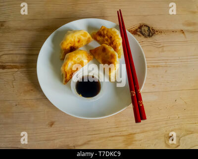 Japanese food Prawn and Mangetout Gyozas with Ponzu Dip from M&S Food, on a white plate with red chopsticks - Stock Image