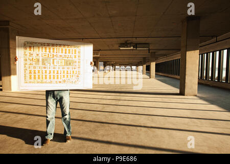Businessman holding up plans for new office space standing in the middle of the empty raw space. - Stock Image
