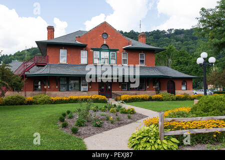 COUDERSPORT, PA, USA-10 AUGUST 18:  The town's old train station, with a colorful, carefully manicured lawn. - Stock Image