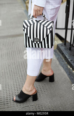 Woman in white culottes holding striped handbag, low section - Stock Image