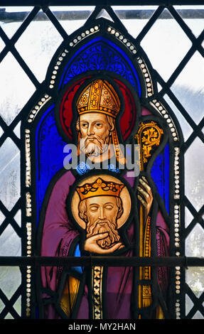 Saint Cuthbert with the head of Saint Oswald. Stained glass window, Parish Church of Saint Kentigern, Great Crosthwaite, Cumbria. - Stock Image