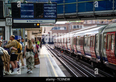 A train sits in the platform at Earl's Court London Underground Station. - Stock Image