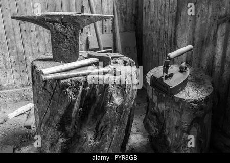 Antique anvil and hammers in a workshop in old Swedish farm in northern Sweden - Stock Image