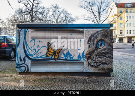 Berlin Wilmersdorf..Paintings & artwork disguise & decorate utility boxes in a suburban street. A cat looking at a butterfly - Stock Image