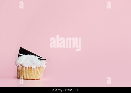 Pretty coconut frosted cupcake decorated with a wedge of chocolate against a pink background. - Stock Image